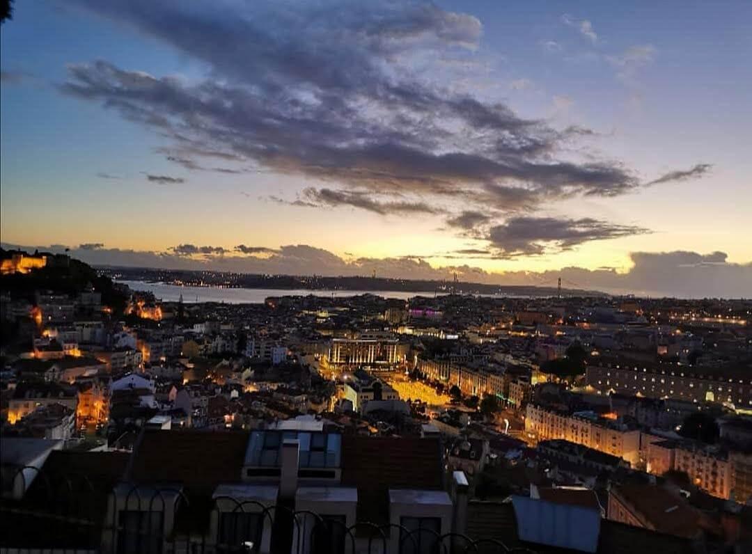 Tmavé mesto a hore jasná obloha zo zapadajúcim slnkom
