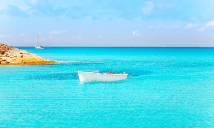 Tyrkysové more s bielym člnom uprostred