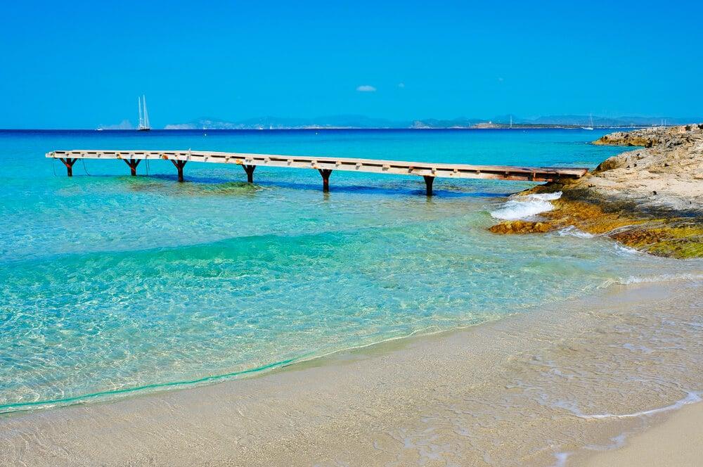 Pláž s modrým nebom a tyrkysovou vodou, krátky mostík na mori