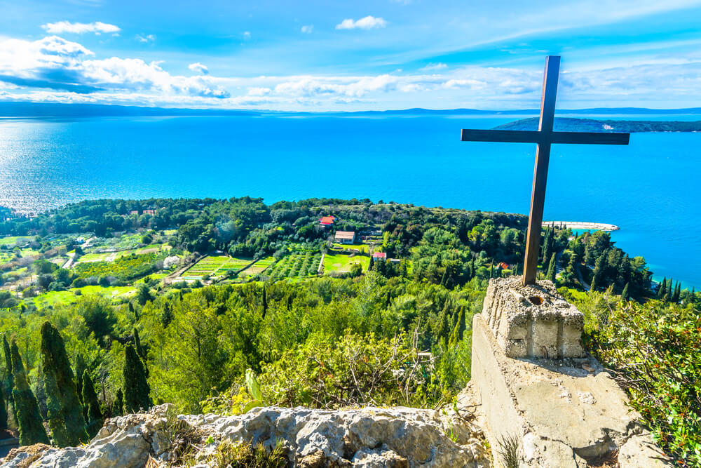Kríž a pred ním zelené lúky a jasno-modré more
