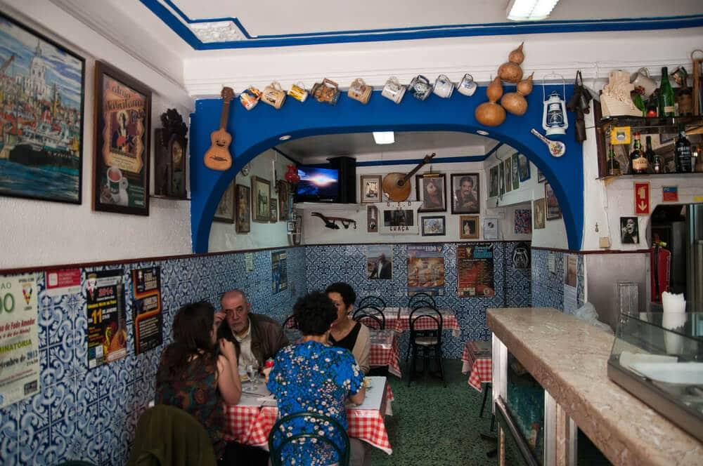 Malá miestnosť obložená modrými kachličkami na vrchu starodávne šálky zavesen a na stenách rôzne obrazy