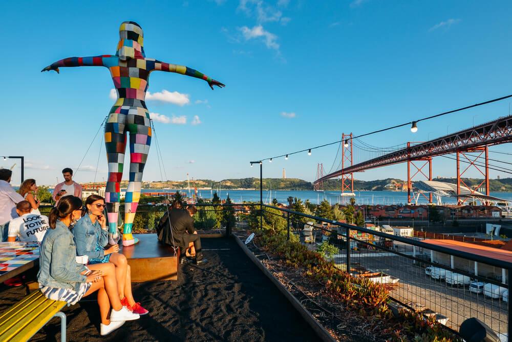 Modrá obloha, výhľad na most a socha farebnej ženy