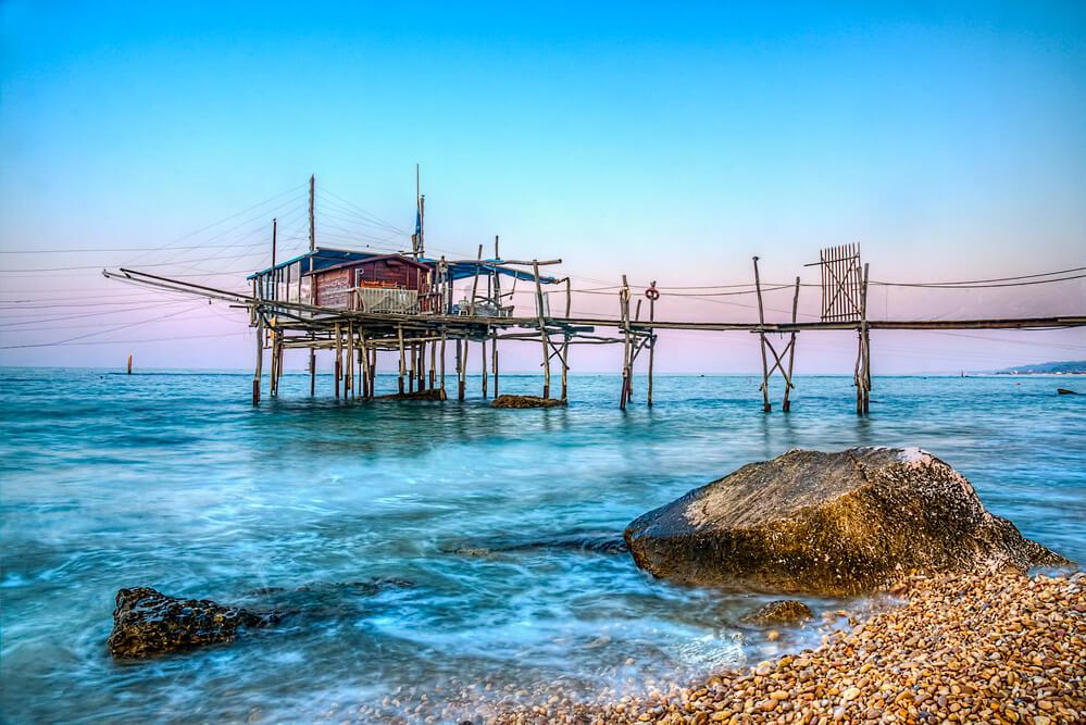 Breh mora a v diaľke malý drevený domček s rybárskymi sieťami