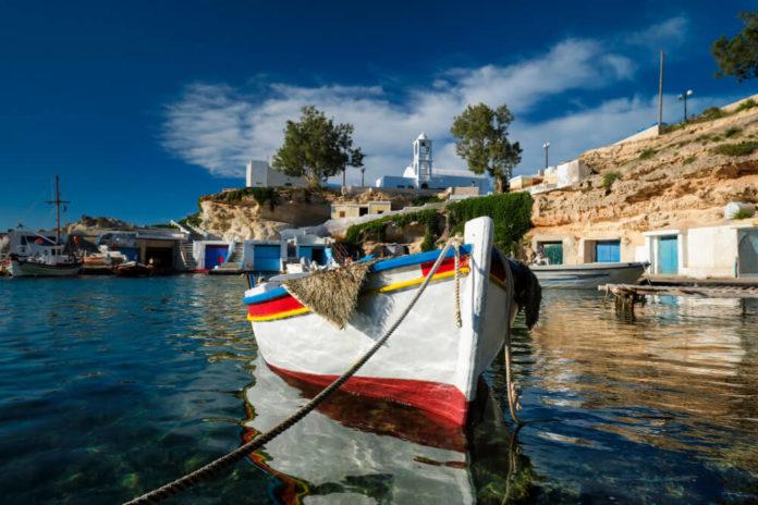 Biela loďka na mori a za ňou kopec s kostolíkom