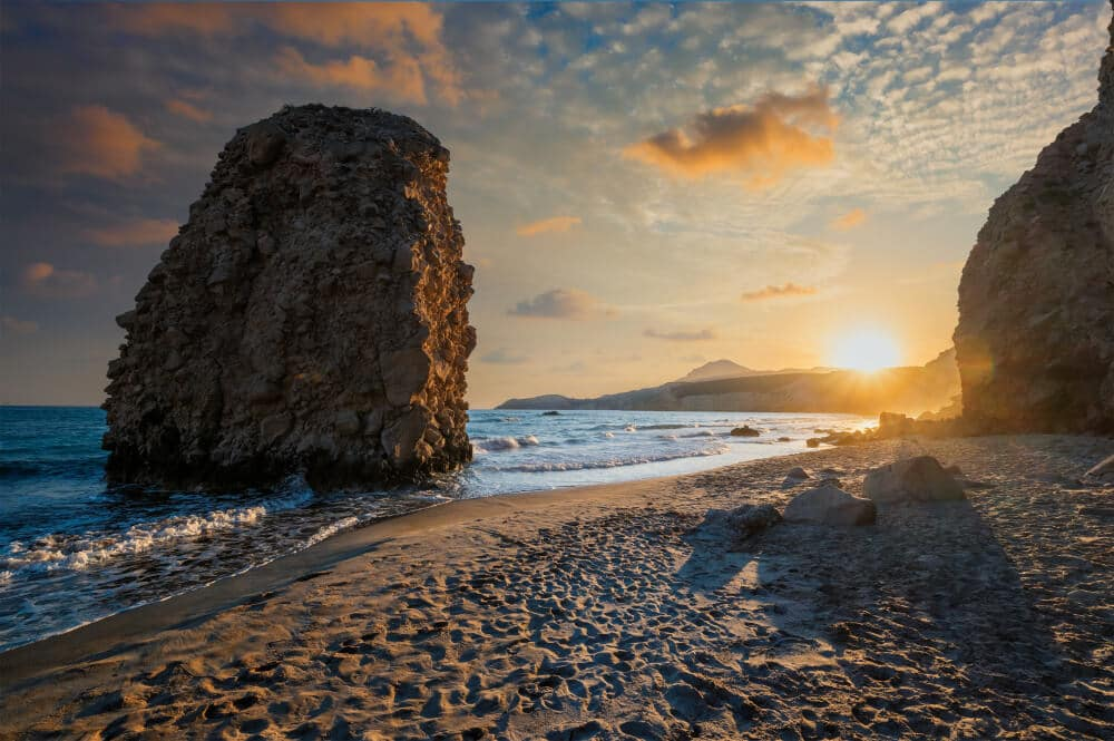 Západ slnka na pláži skala a more