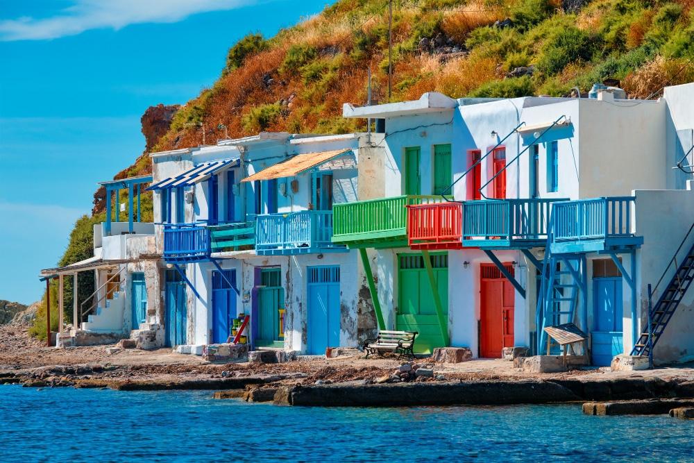 Domčeki pri mori bielej farby a s modrým, zeleným a červeným zabradlím a vchodovými dverami