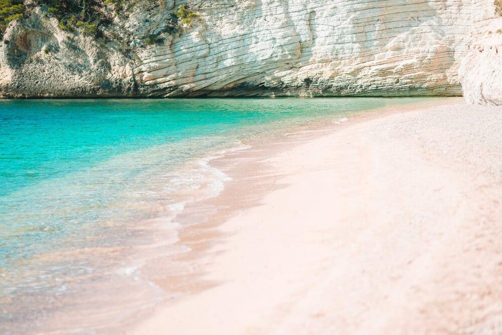 Biely, jemný piesok a vápencová skala na pobreží tyrkysového mora