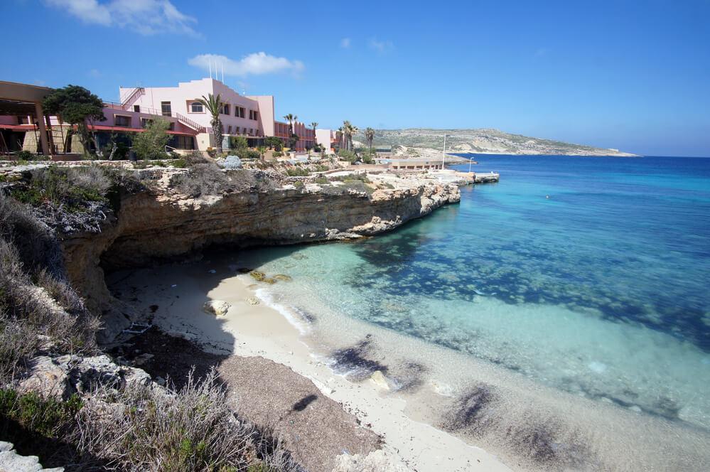 Skala pod ňou pláž s morom a vzadu hotel ružovej farby