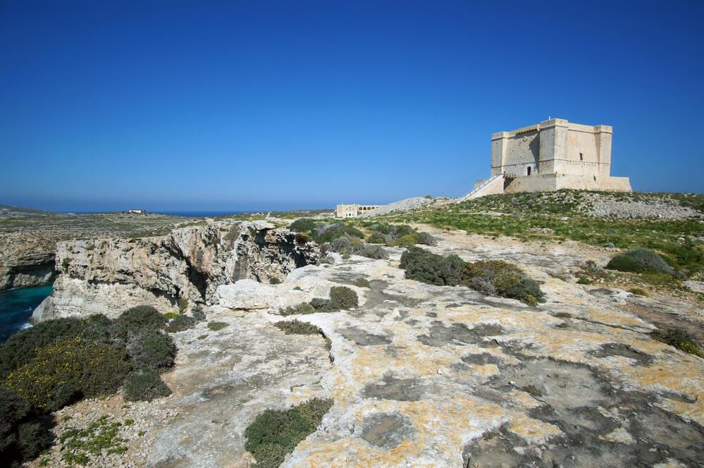 skalnatý povrch a v diaľke veža santa marija- malá veža v tvare kocky telovej farby