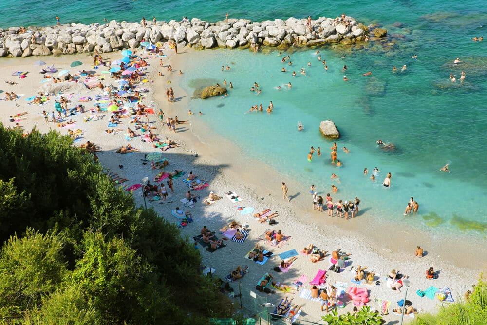 Pláž s bielym pieskom, množstvom ľudí na pobreží krásneho priezračného mora