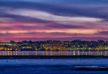Západ slnka, modro-ružová obloha, more a v diaľke tiahnuce sa mesto