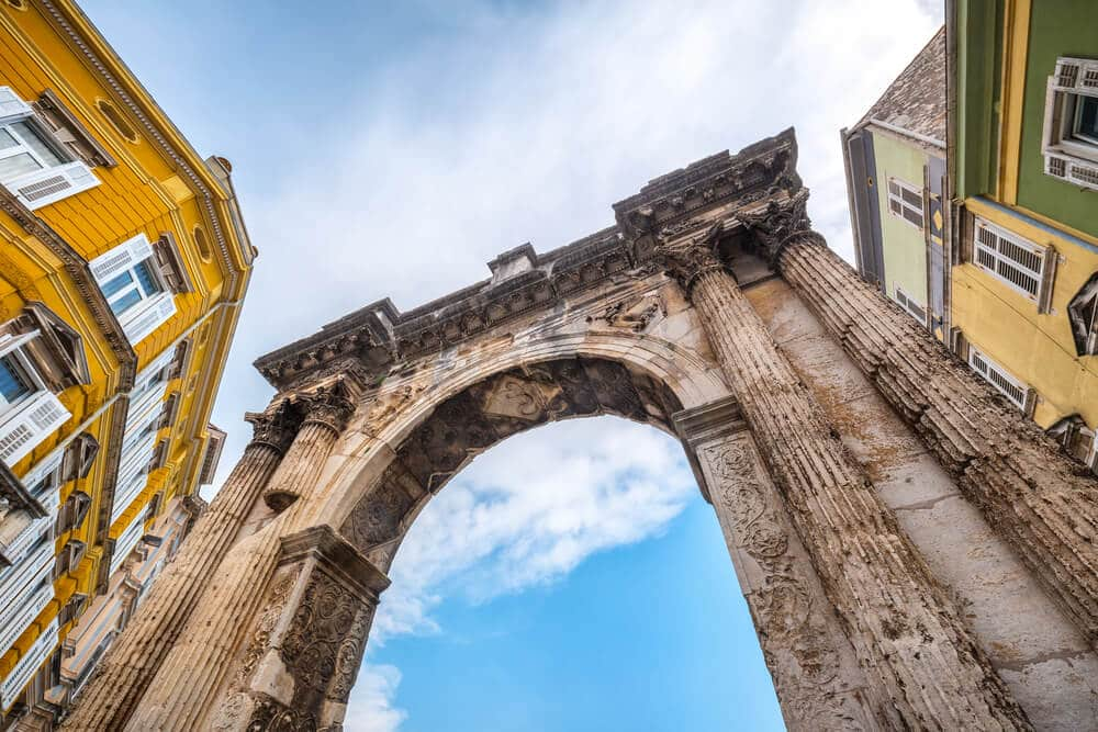 Staroveký oblúk obklopený žltými budovami