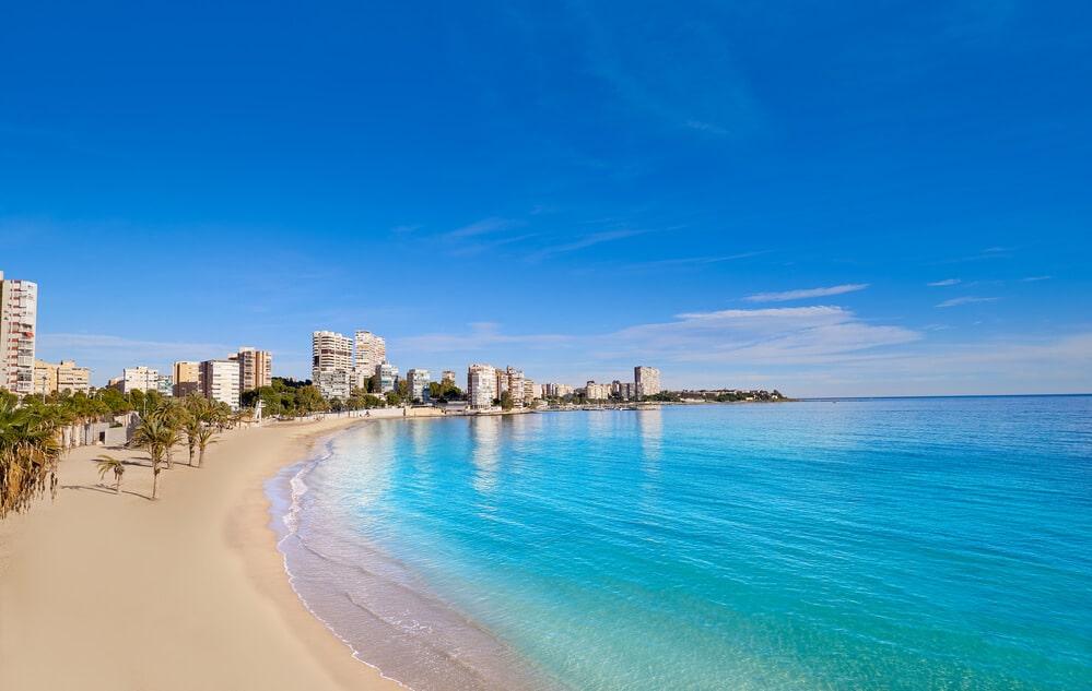 Piesková pláž s tyrkysovím morom a vzadu vysoké budovy