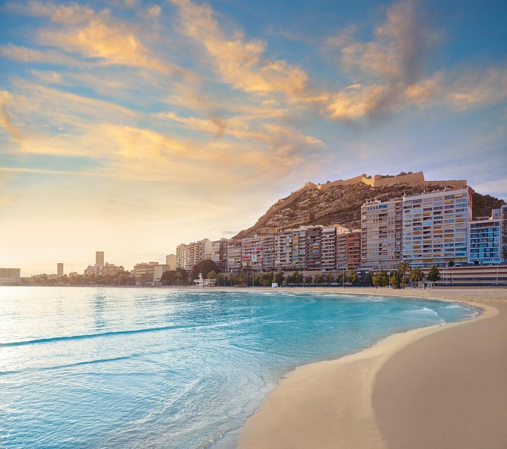 Pohľad z pláže styrkysovám morom na hotely a na zrúcaninu hradu na kopci