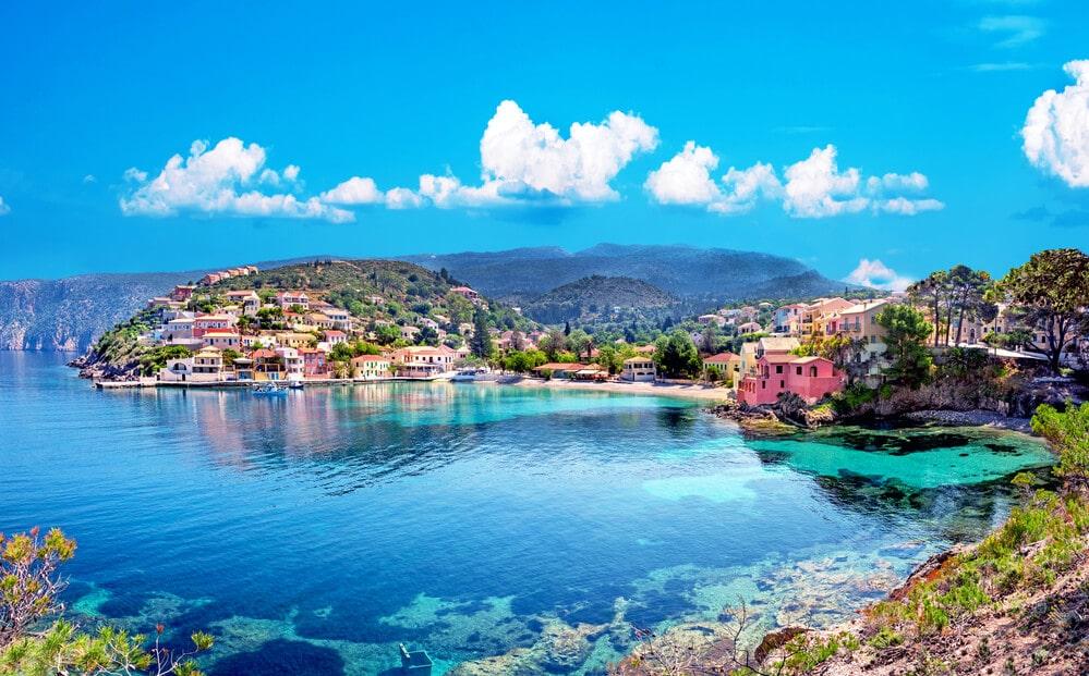 Pohľad na malá dedinku vyrastenú na strmom brehu mora s krásnymi farebnými domami a nádhernou prírodou
