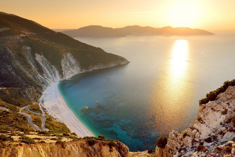 Pohľad zo skaly na pláž s bielym pieskom a dvojfarebným morom