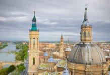 Dve veže tiahnuce sa do výšky, so striebornou a zelenou strechou, za nimi mesto, naľavo od veží je most a rieka