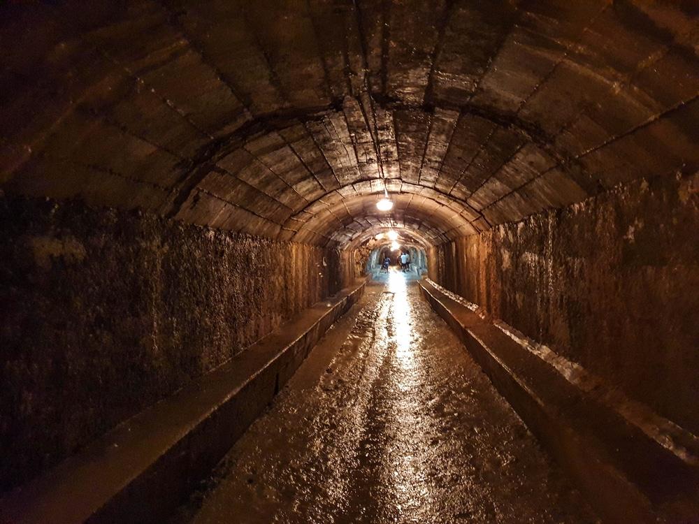 Podzemná chodba, kde na konci tunela svieti žlzé svetlo, chodba pôsobí vlhko a mokro