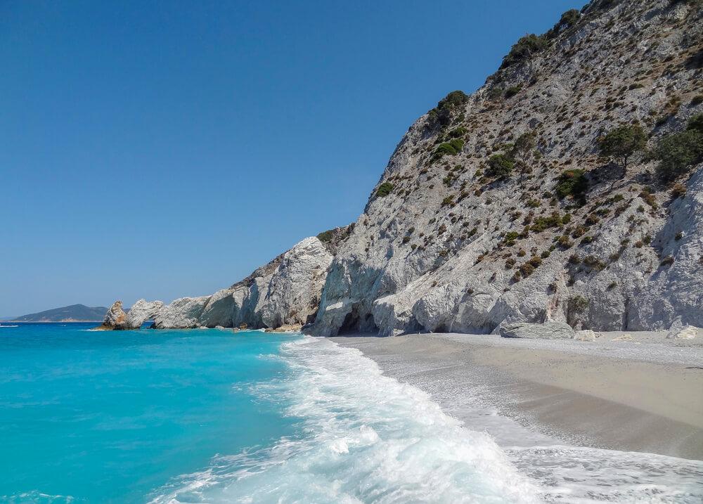 Pláž s bielym pieskom a slabomodrou farbou mora, nad plážou sa do výšky tiahnu vysoké sivé skaly