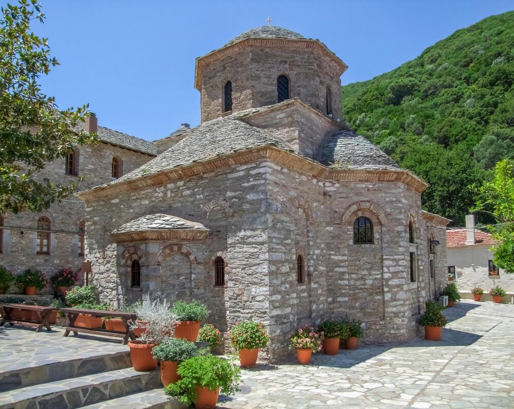 Kamennú kostol na vydlaždenej ploche, kde sú kvetiny v črepníkoch a lavičky , za ním sa tiahne vysoký kopec hory