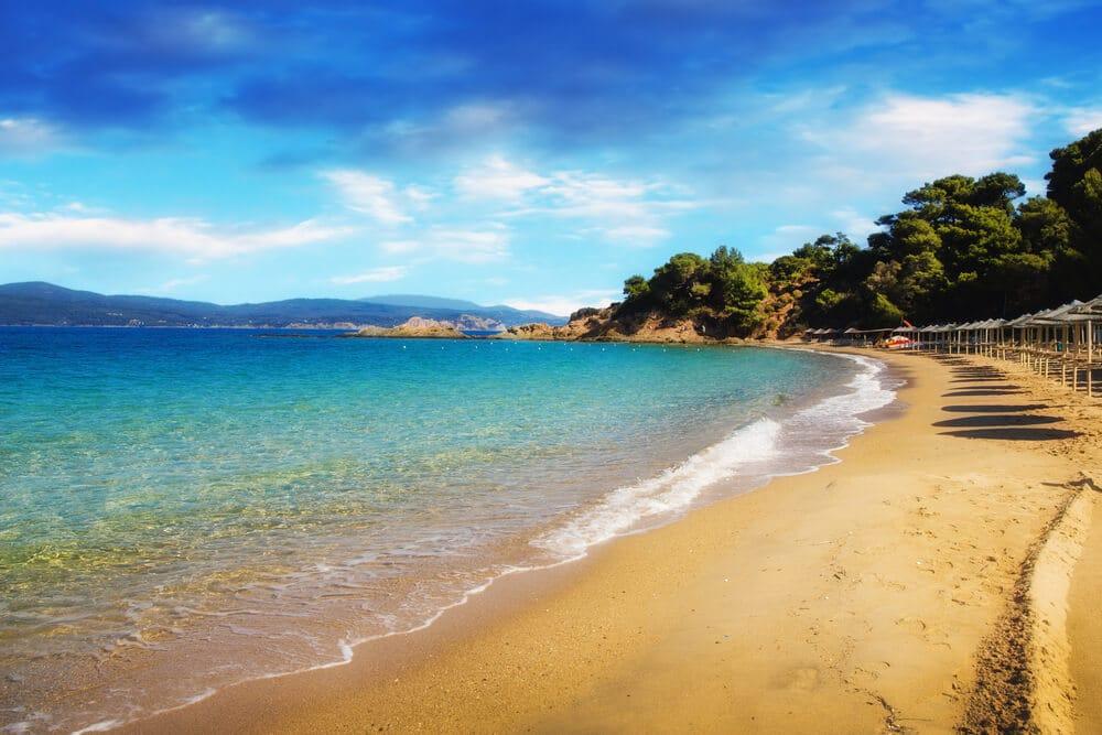 Pláž so žltým pieskom so slabomodrou vodou mora na začiatku a za ním tmavomodrá voda mora, na pláži sú slnečníky a za nimi ihličnaté stromy