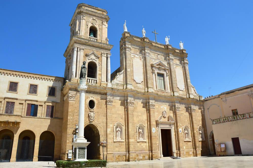 Hnedý kostol v tvare obdĺžnika, s prázdnymi výklenkami a navrchu so sochami Panny Márie