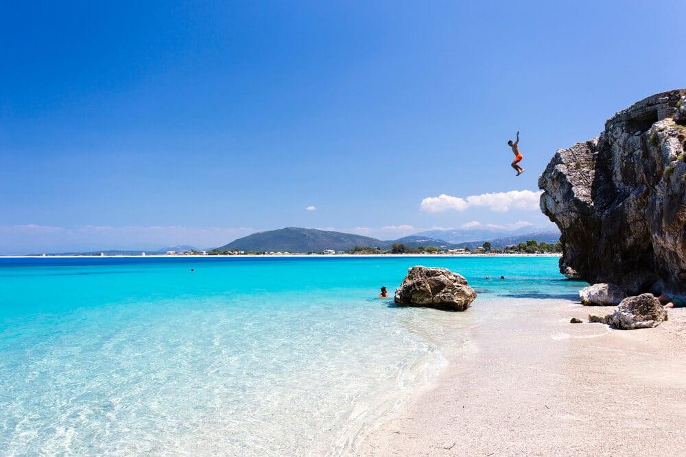 Pláž so skalou, z ktorej skáče chlapec do tyrkysového mora
