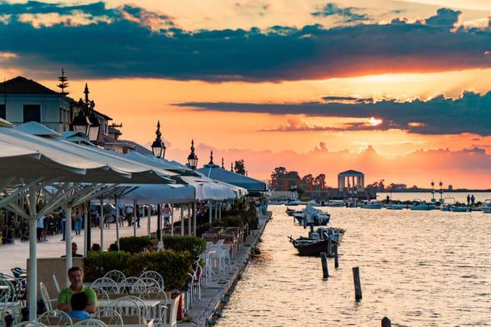 reštaurácia so slnečníkmi na pobreží pokojného mora s malými loďkami a zapadajúce slnko vytvára ružovú oblohu