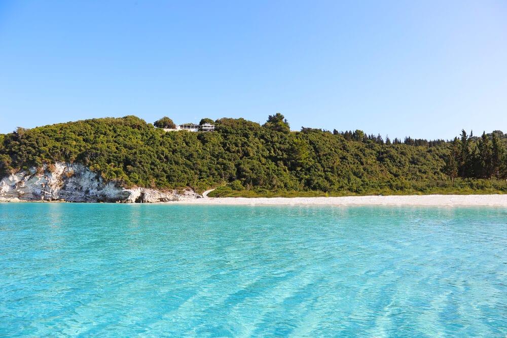 Krásna bledunko modrá hladina mora a skaly obrastené zeleňou