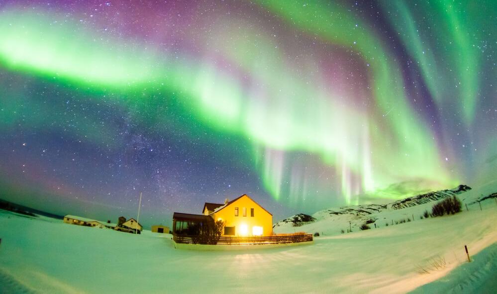 Na zasneženej zemi s chlúpkou je na oblohe fialovo modro zelená polárna žiara