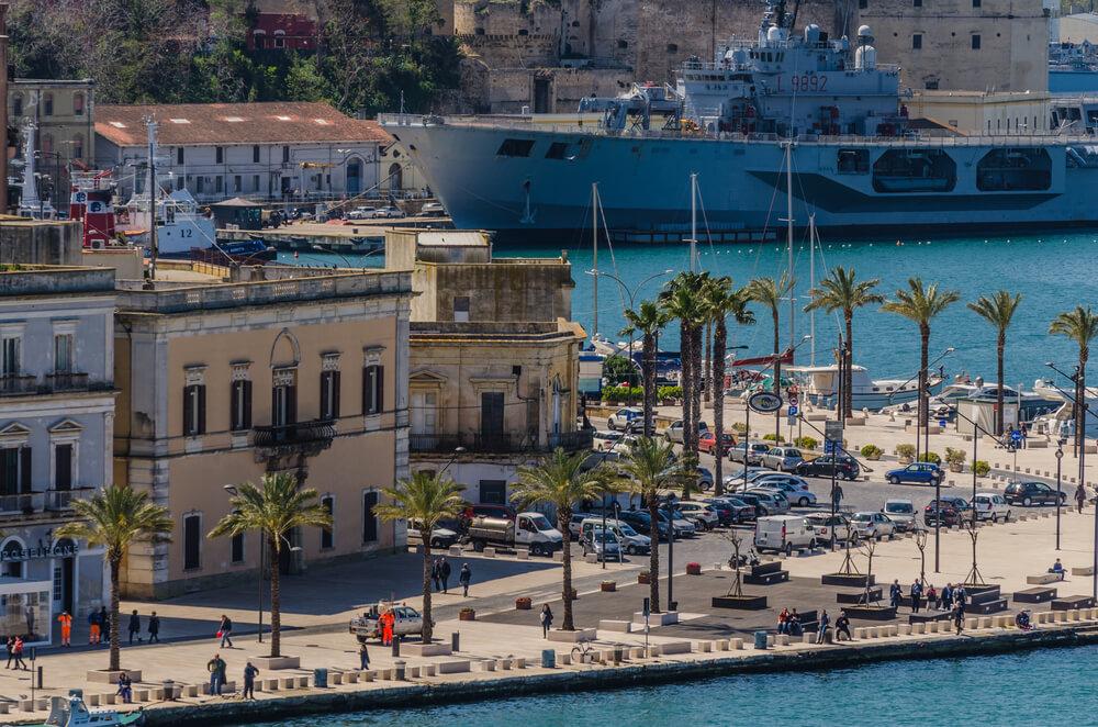 Pohľad na prístav v Brindisi, staré domy, palmy a výletná loď v zadu