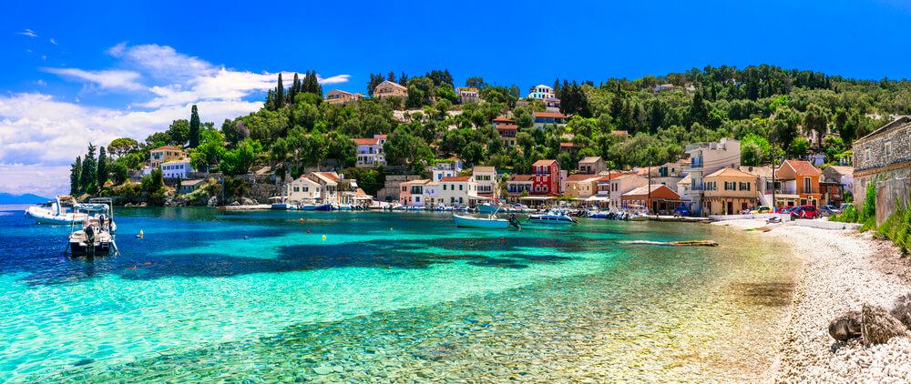 Pohľad na malú prímorskú dedinku s farebnými domčekmi pri pobreží čistého mora