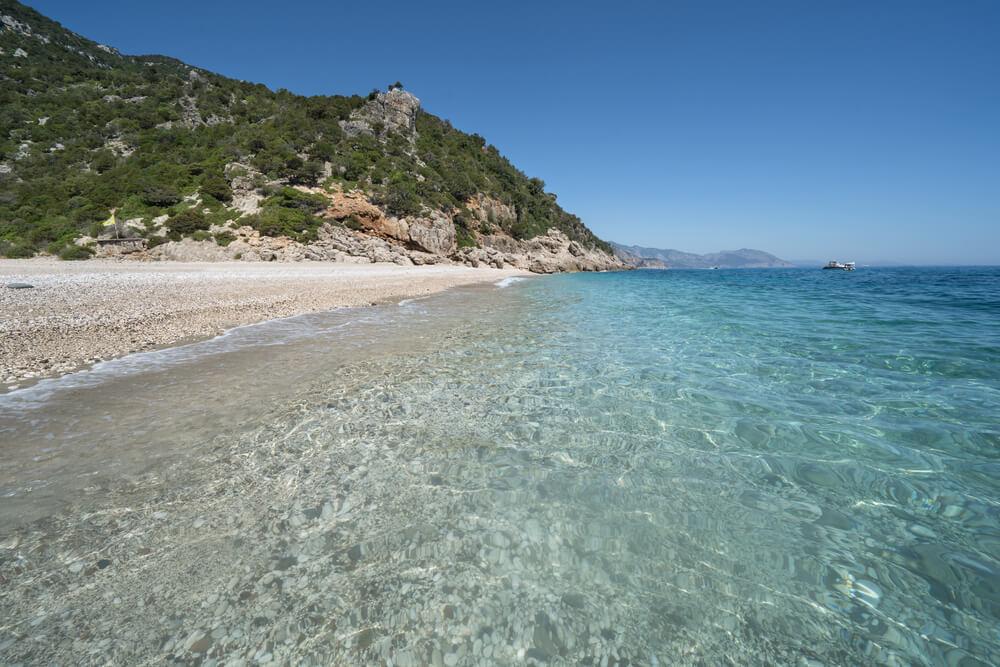 Pphľad na kamienkovú opustenú pláž s priezračným morom