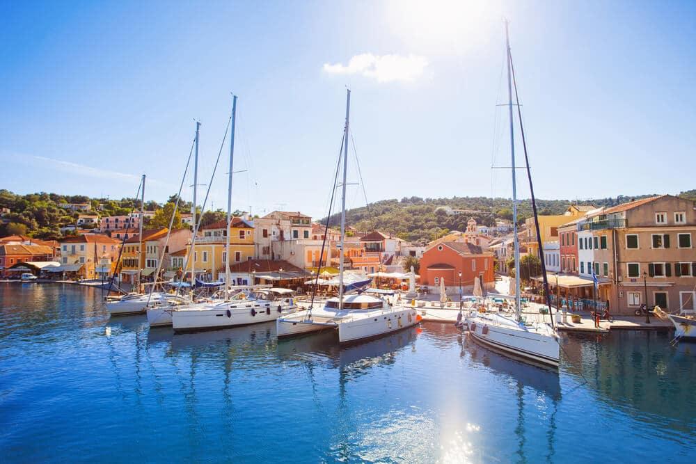 Pohľad z mora na menší prístav s piatimi plachetnicami, za ktorými sú farebné domčeky
