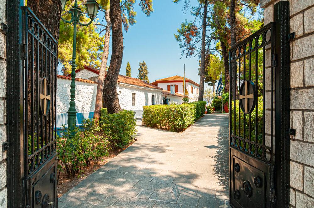 Vstupná čierna bráno dedúce cez vydláždený chodník k podlhovoastej budove s oranžovou strechou, ku kláštoru Panagia Faneromeni
