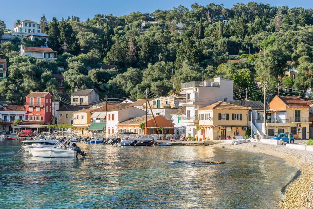 Malá prímorská dedinka s farebnými domčekmi, nad ktorými sa vypína malý kopec s bohatými stromami, na pobreží sú odparkované motorové člny a loďky