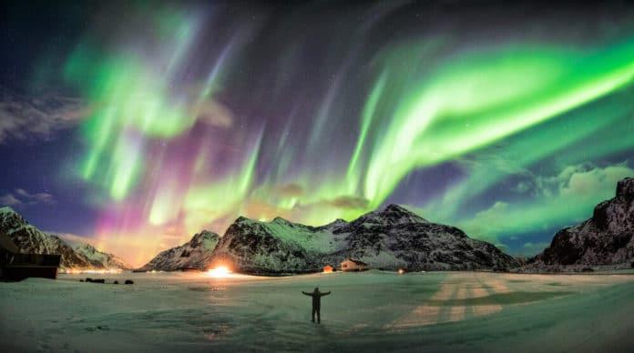Fialovo zelená polárna žiara na tmavej oblohe nad zasneženými skalami, pod ktorými stojí na snehu muž s otvorenými rukami