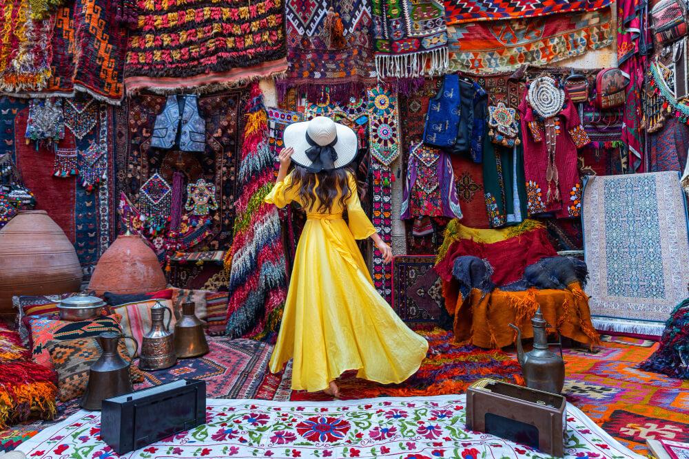 Žena v dlhých žlrých šatách stojí pred predajňou tkaných kobercov a iných ručne šitých vecí