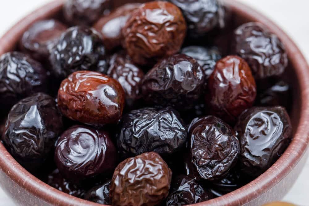 Tmavé sušené olivy vhnedej miske na bielom stole