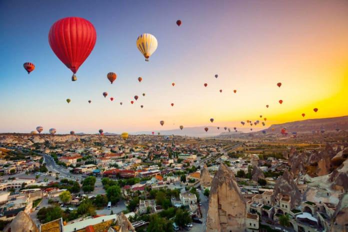 Farebné teplovzdušné balóny lietajúce nad malebnou krajinou pri západe alebo východe slnka